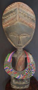 Présentation d'un collier en tissu wax sur une poupée Ashanti